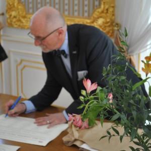 Jan Malicki składa podpis na dyplomie